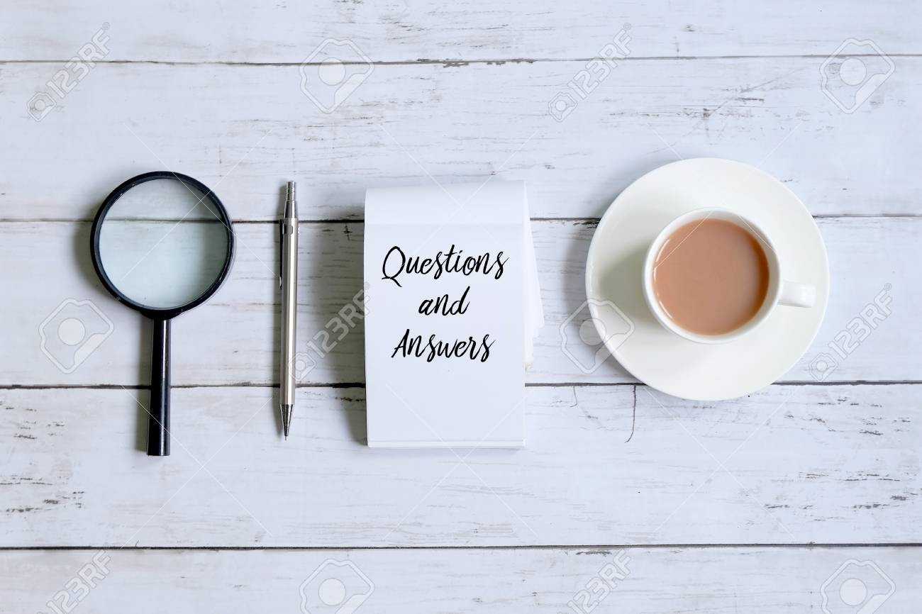 Top view of a cup of coffee,magnifying glass,pen and notepad written with 'QUESTIONS AND ANSWERS' on white wooden background. - 94887895