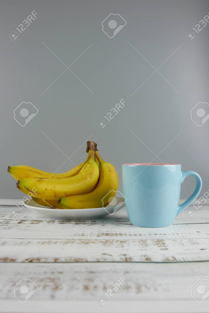 Bunch Of Bananas And A Cup On Wooden Background Copy Space For Stock Photo Picture And Royalty Free Image Image 129915179