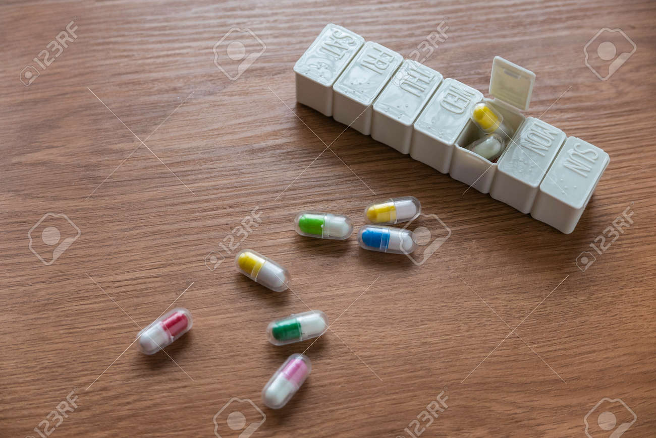 Selective focus of pill box with spilled pills on wooden table. - 169596819