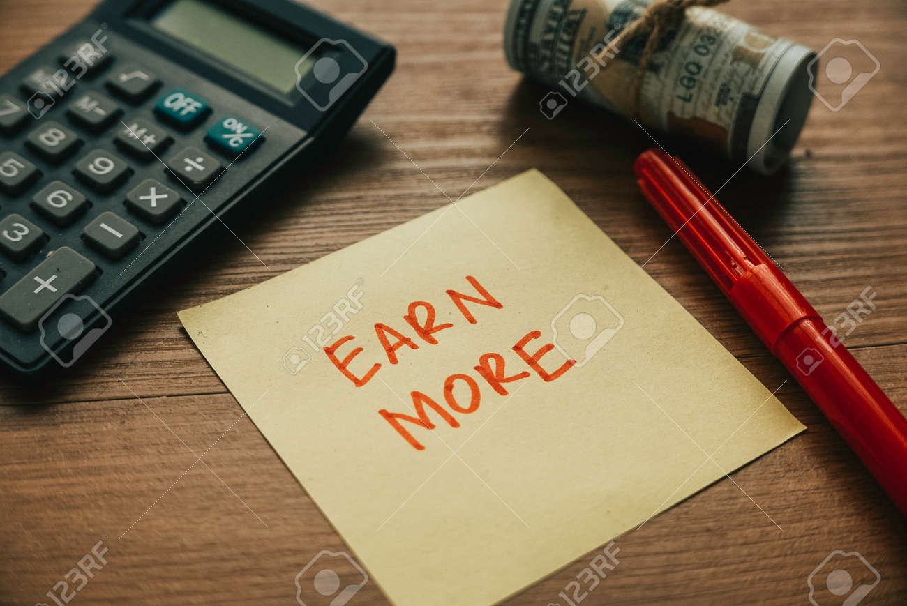 Selective focus of calculator,money pen and paper written with Earn More. - 169596823