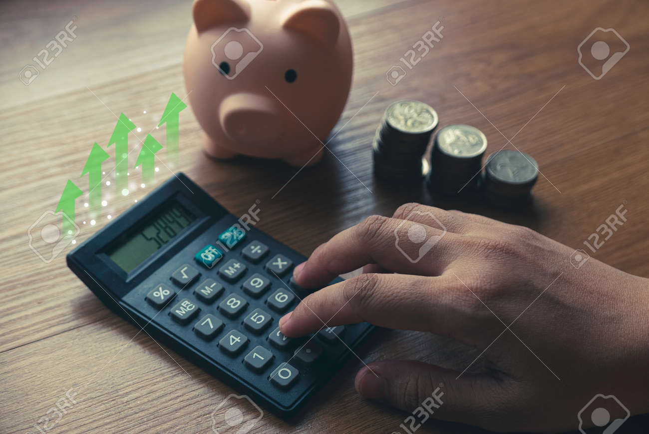 Business and finance concept with hand pressing calculator , a stack of coins and piggy bank. - 169596852