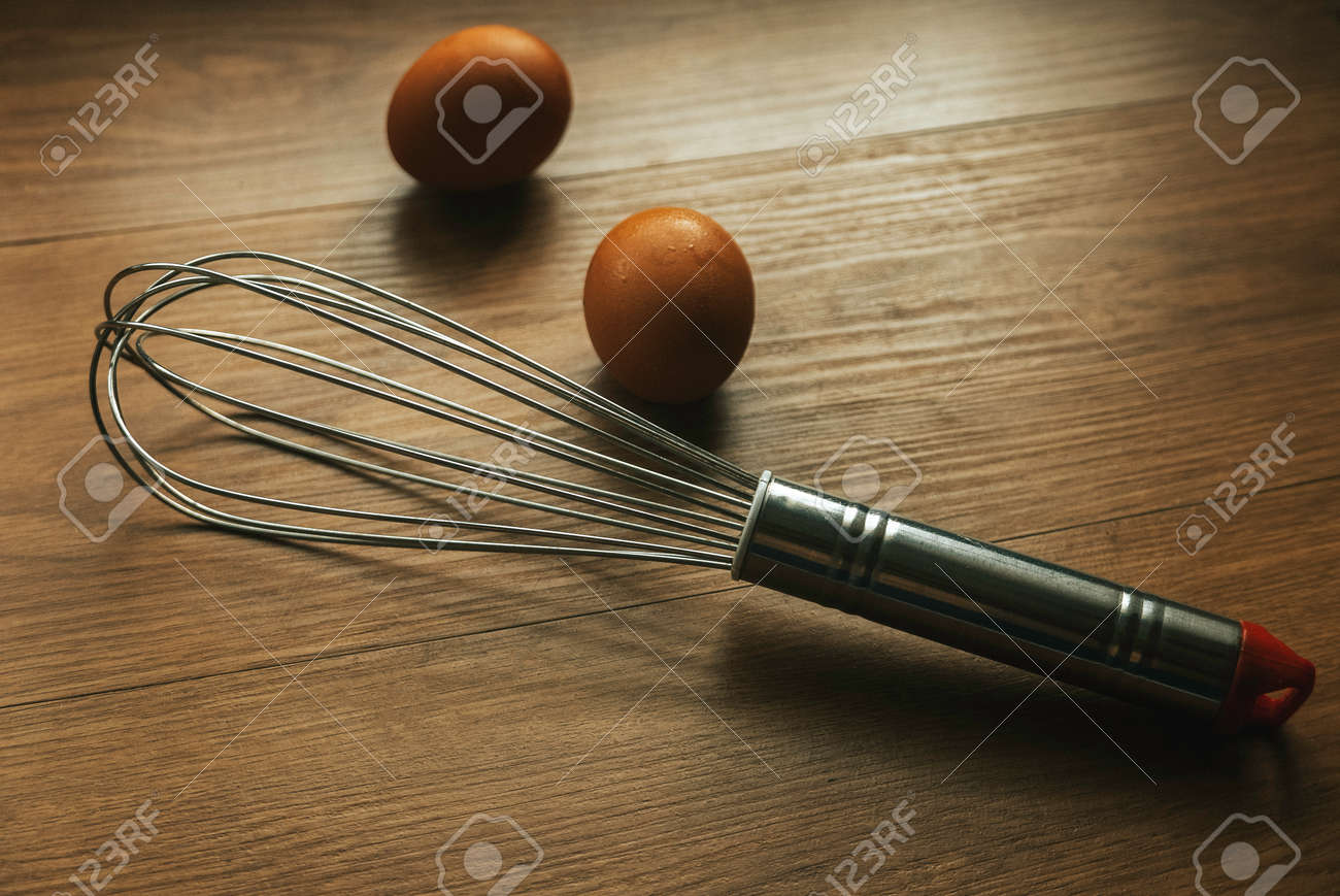 Stainless Steel of whisk and an egg on wooden background. - 169596864