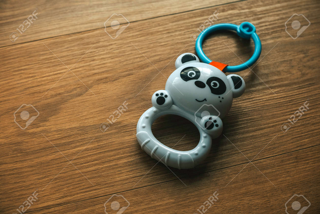 Panda baby rattle toy isolated on a wooden background. - 169597214