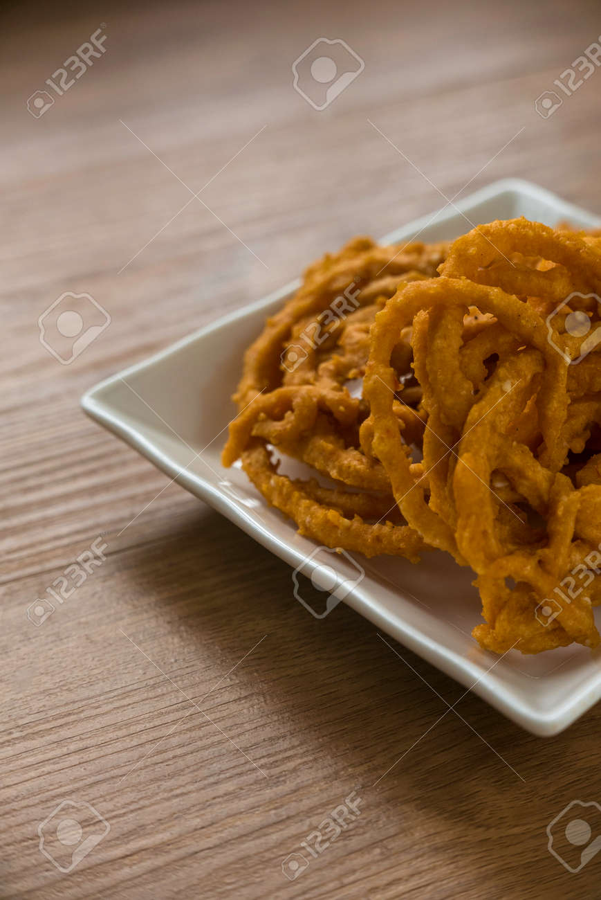 Murukku is a savory, crunchy snack originating from the Indian subcontinent.Its an Indian traditional tea time snack chakli, a deep fried snack, It is known as Chakali, Muruku, Murkoo, Chakri. - 169597216