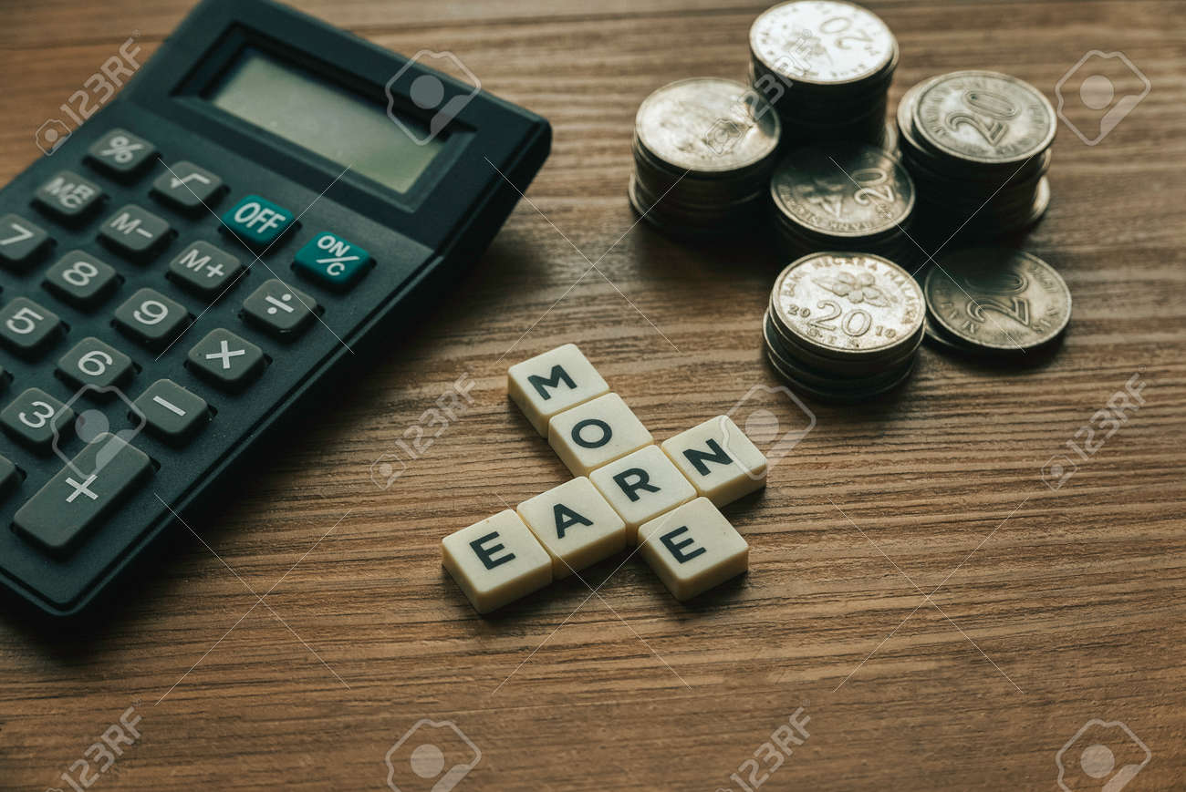 Selective focus of stack of coins,calculator and crossword alphabet of word Earn More on wooden background. - 169597222