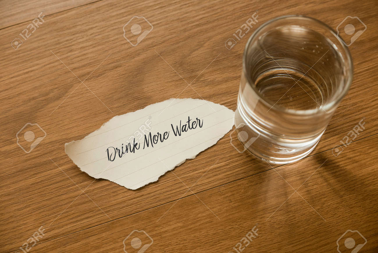 Top view of a glass of drinking water with a paper written with Drinking More Water on wooden background. - 169597266