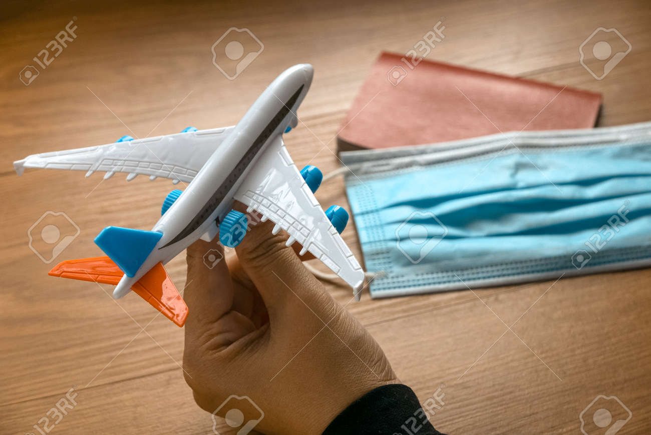 Hand holding a toy plane with a passport and face mask on the travel.Concept of travelling during pandemic and new normal. - 169597302