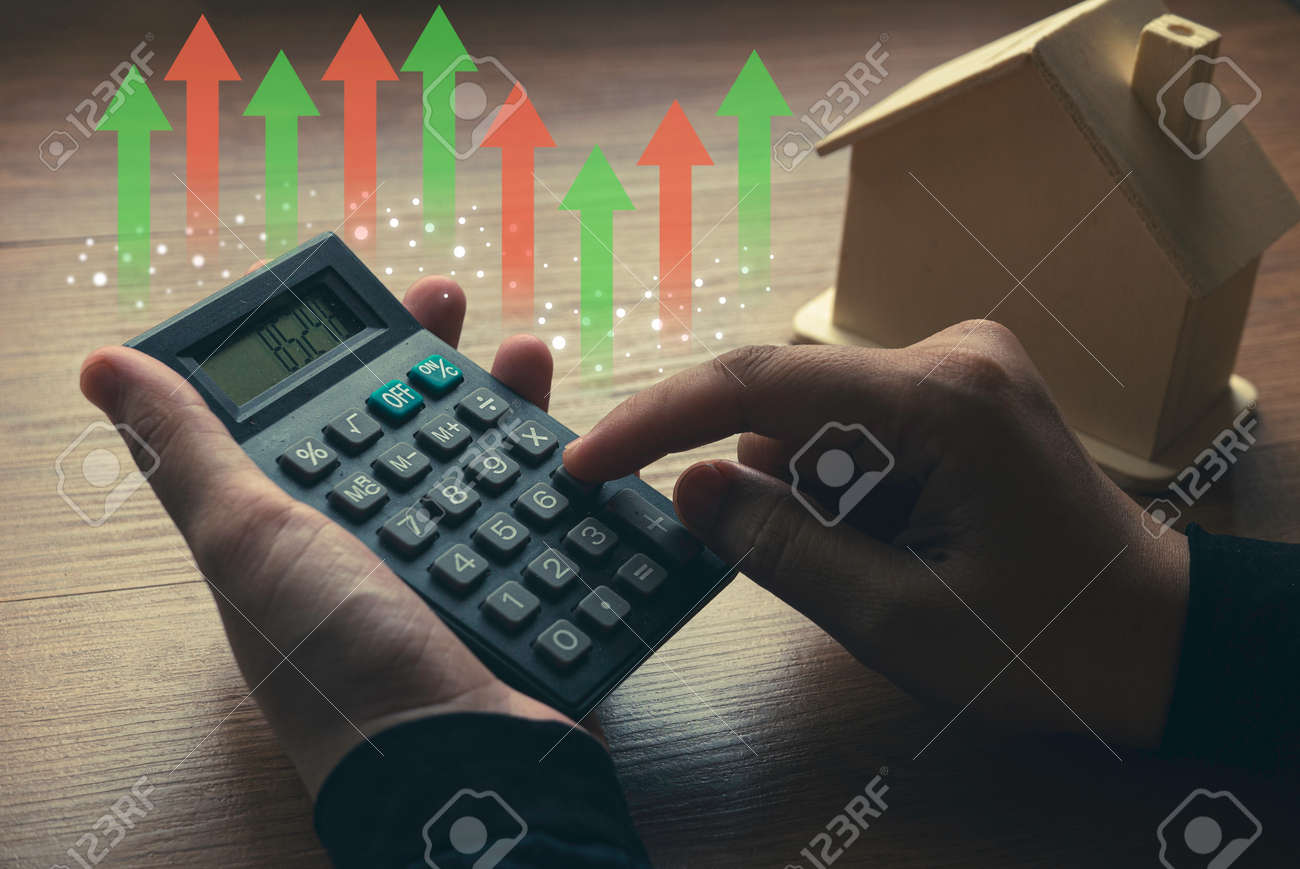 Business, finance, property and real estate concept with hand holding a calculator doing calculation and house model with graph at the background. - 169597307