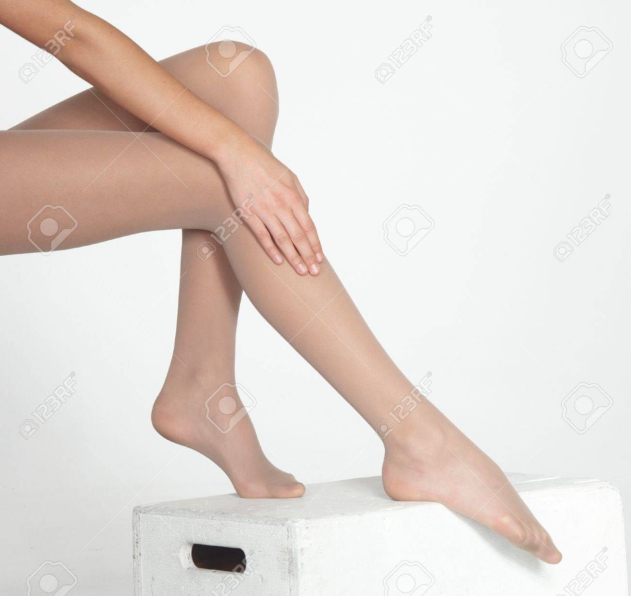 de7a98c2874 Stock Photo - Woman s Legs Wearing Sheer Nude Pantyhose Isolated Against a  White Studio Background