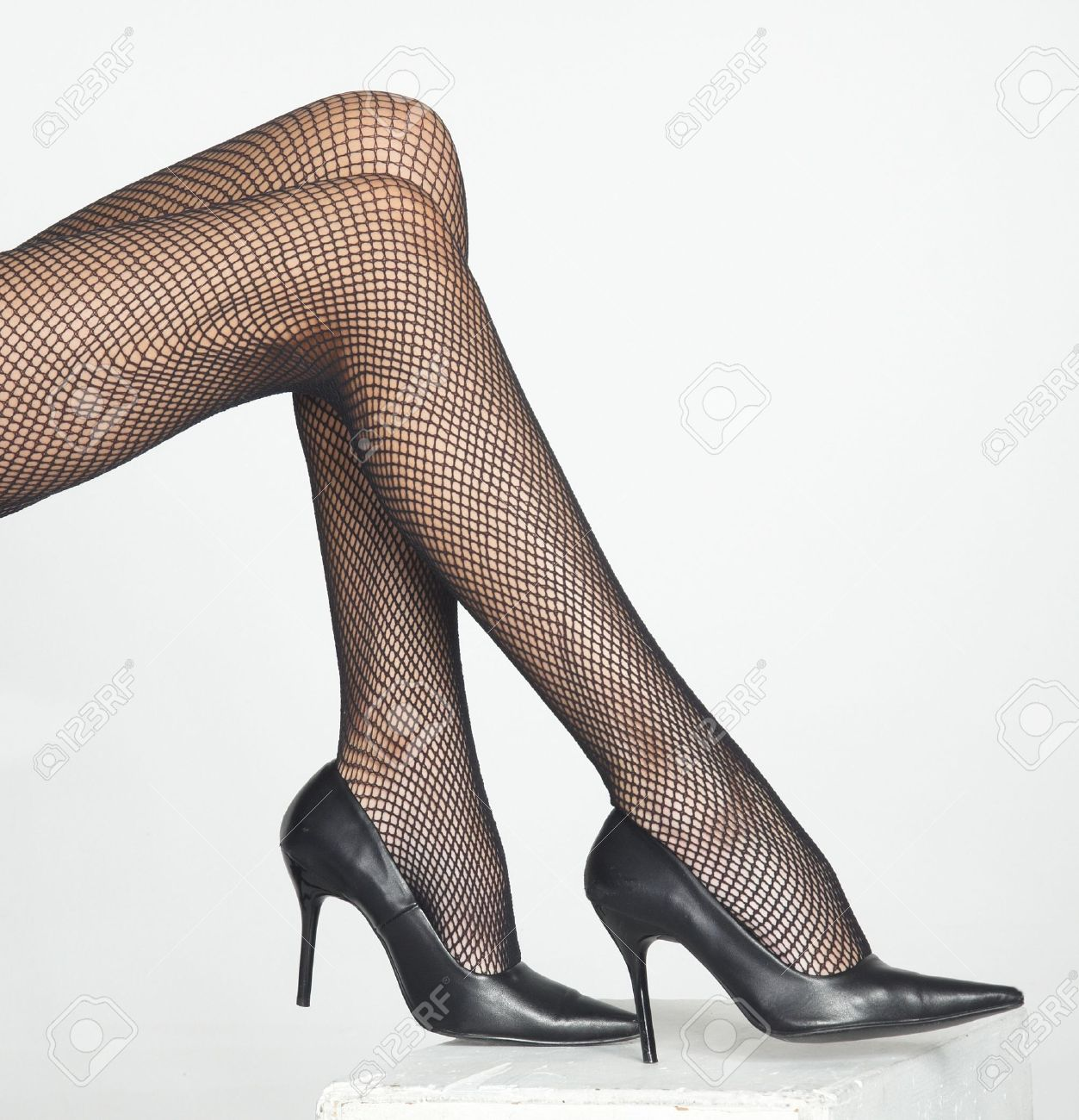 bc96c4353678 Woman s Legs Wearing Black Fishnet Pantyhose and Black High Heels Stock  Photo - 12830359