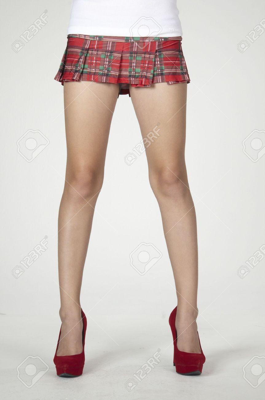 723fa7e6aa4227 Gros plan sur les jambes de femme dans une fille mini jupe à carreaux de  l'école et des talons hauts rouges