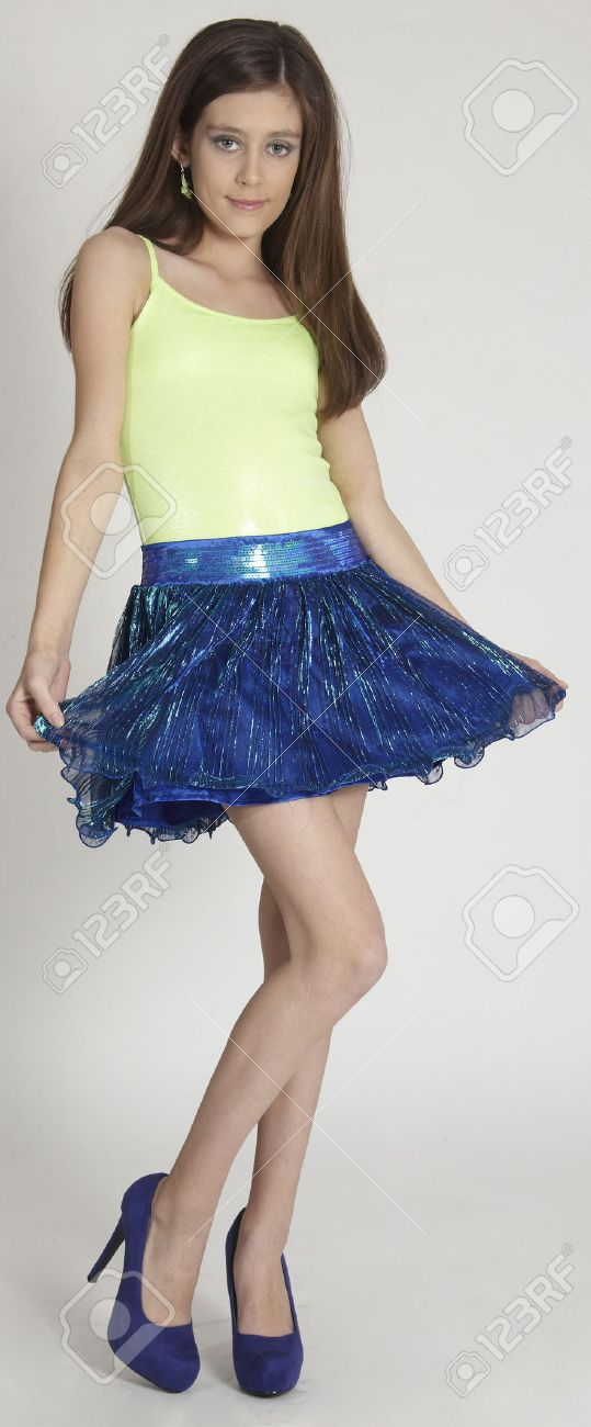 94dd1e7f1 Stock Photo - Teen Girl in a Skirt and Heels Against a White Studio  Background