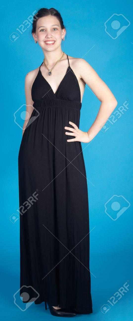 Teen Girl In A Long Black Dress And Heels Against A Blue Background