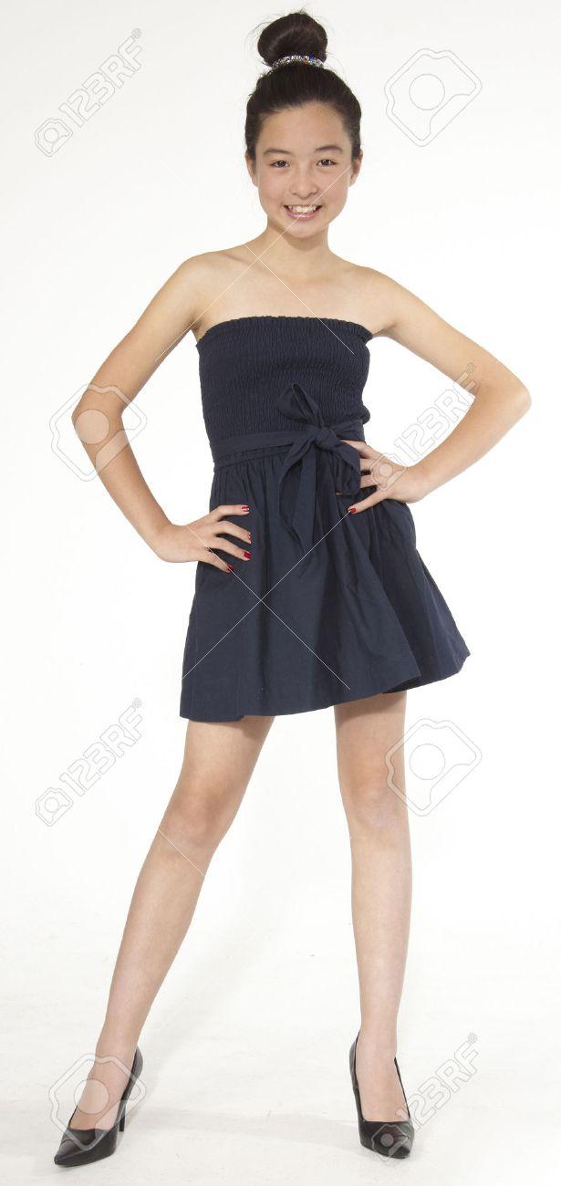 Adolescente De La Muchacha Asiática Posando En Un Vestido Negro Y Zapatos De Tacón