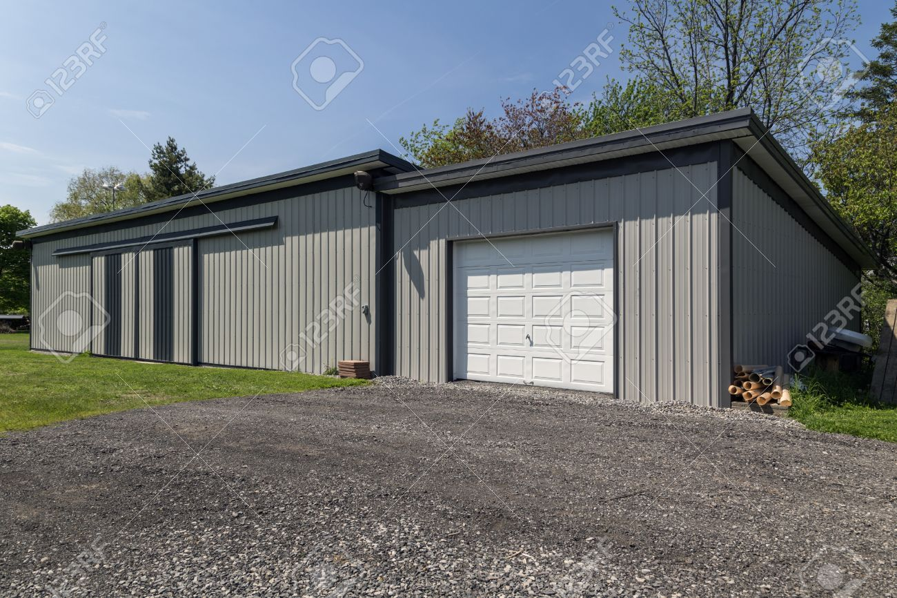 Large Grey Steel Barn In Modern Style. White Garage Door With Gravel  Driveway. Stock