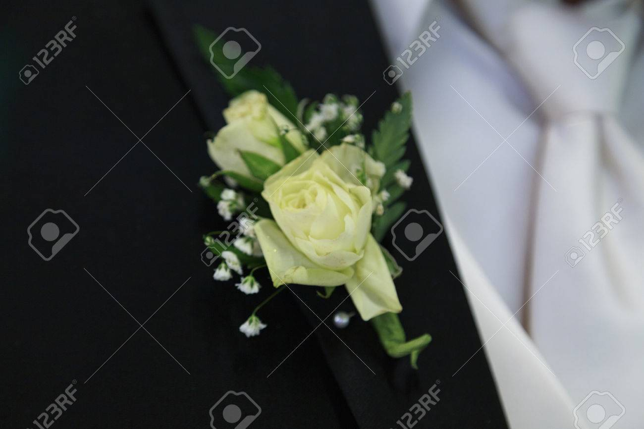 Off white flowers of this grooms boutonniere are pinned to his off white flowers of this grooms boutonniere are pinned to his black lapel stock photo mightylinksfo