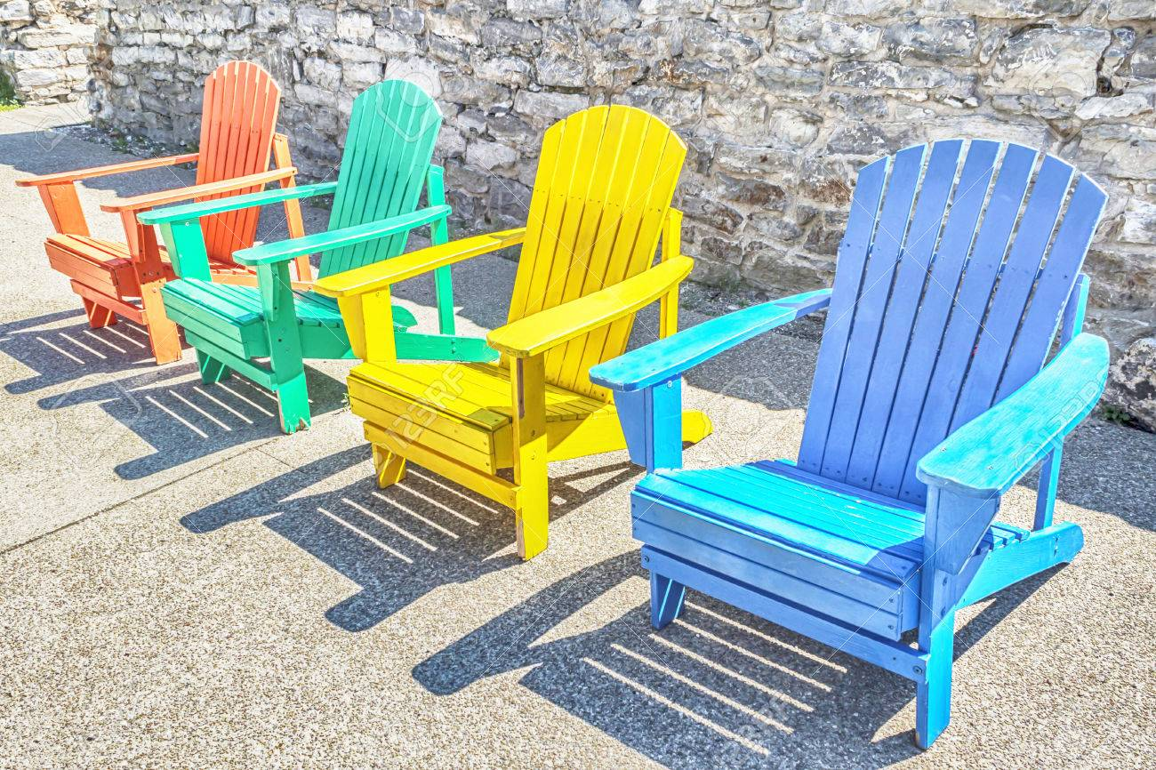 Delicieux Brightly Colored Adirondack Chairs Arranged In A Row. Bright Sun Lights  Them. Stock Photo