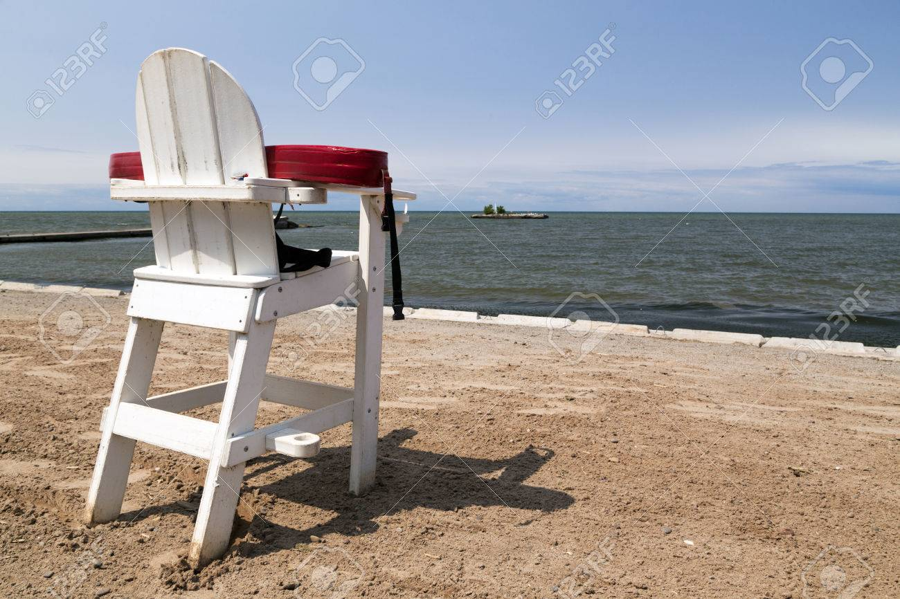 78232658a59f Stock Photo Unmanned White Liuard Chair With Floatation Device On An Empty  Beach
