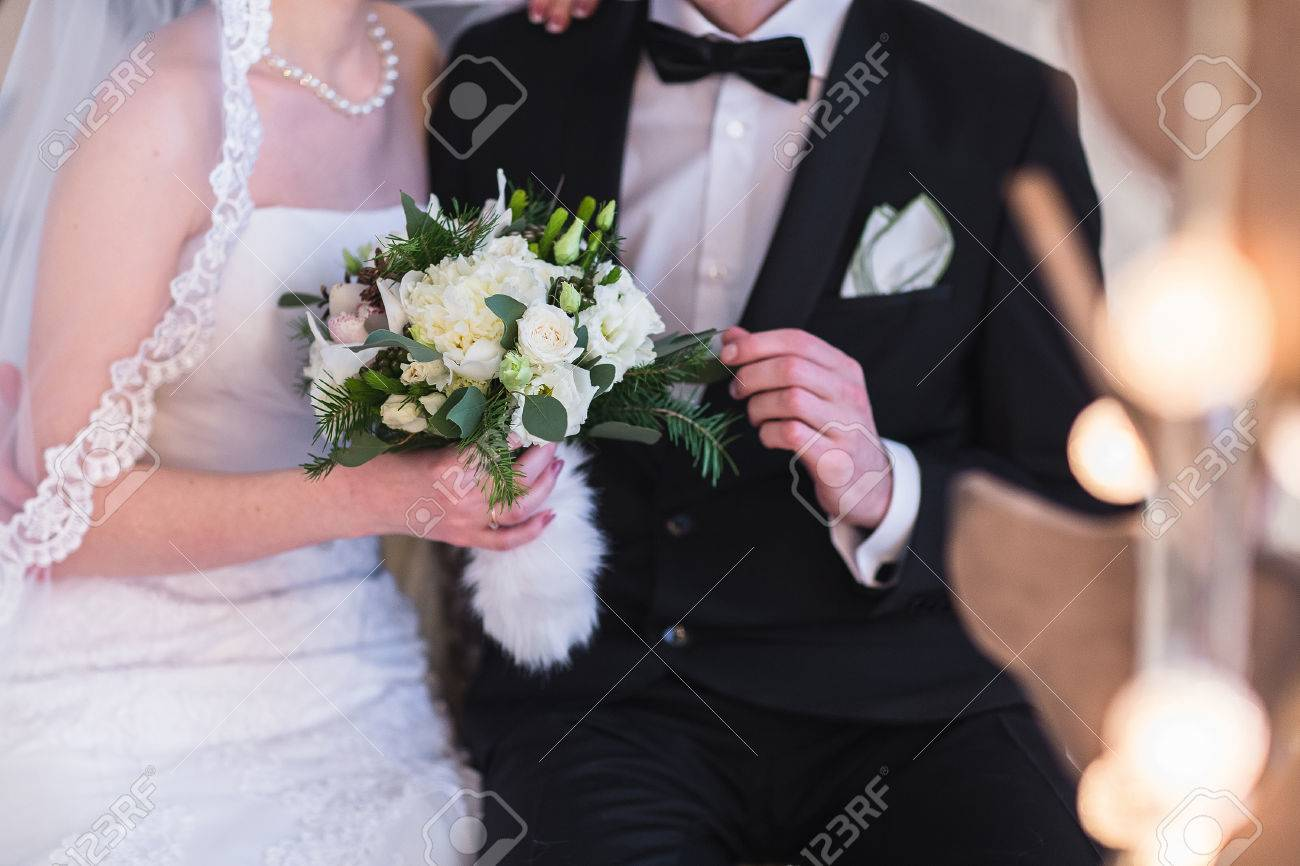 Beautiful winter wedding bouquet. Bridal bouquet with cones, cotton and spruce branches. The bride holds a wedding bouquet next to the groom. - 50241834