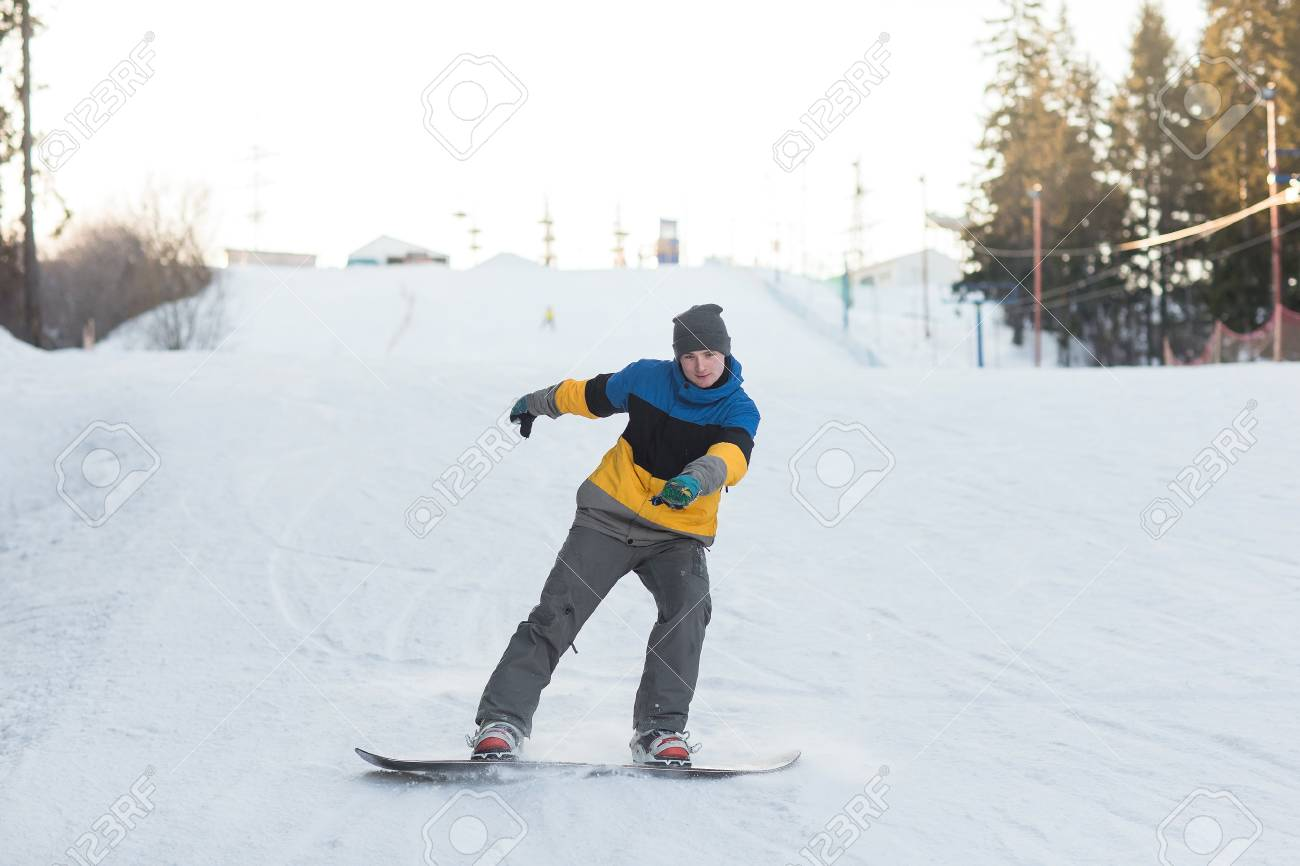 a59f4f37a6c Male snowboarder laying turns on the ski slope snowboarder coming down from  the mountain in winter