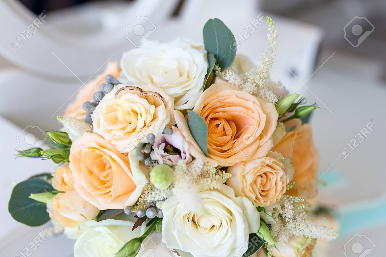 Wedding Rings Lie On The Bridal Bouquet Of Roses. Gold Wedding ...