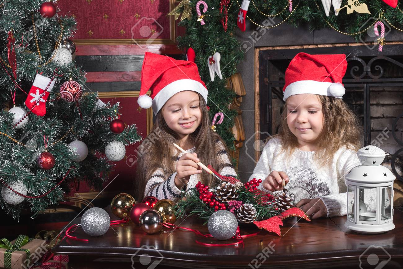 A Christmas Arrangement.Two Girls Sisters Or Friends Decorate A Christmas Arrangement