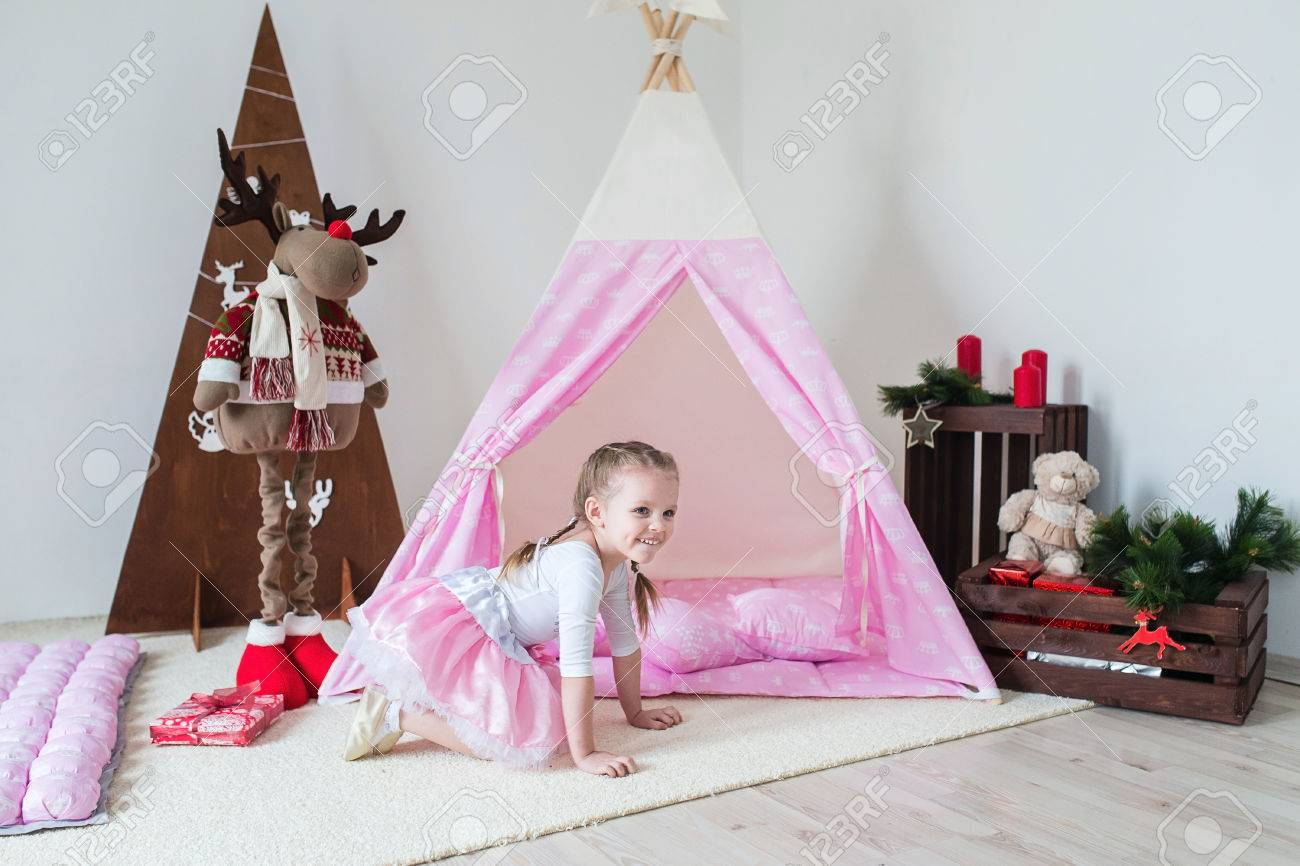 Happy child in a teepee tent. Little girl playing in a tent. Stock Photo & Happy Child In A Teepee Tent. Little Girl Playing In A Tent. Stock ...