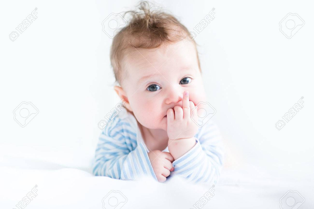 Sweet baby in a blue shirt sucking on its finger Stock Photo - 29559772