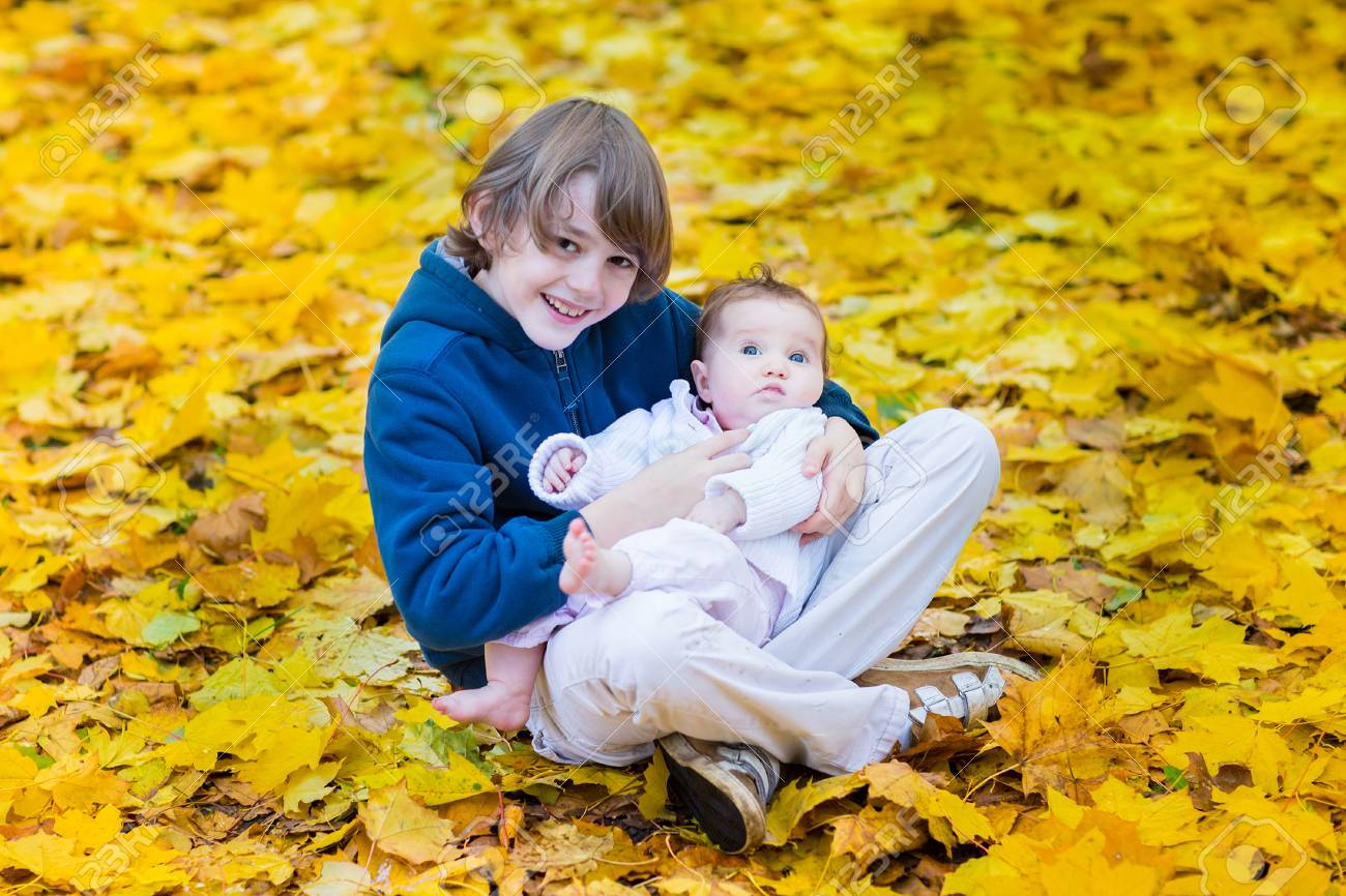 Cute Brother Holding His Baby Sister Playing Between Yellow Maple