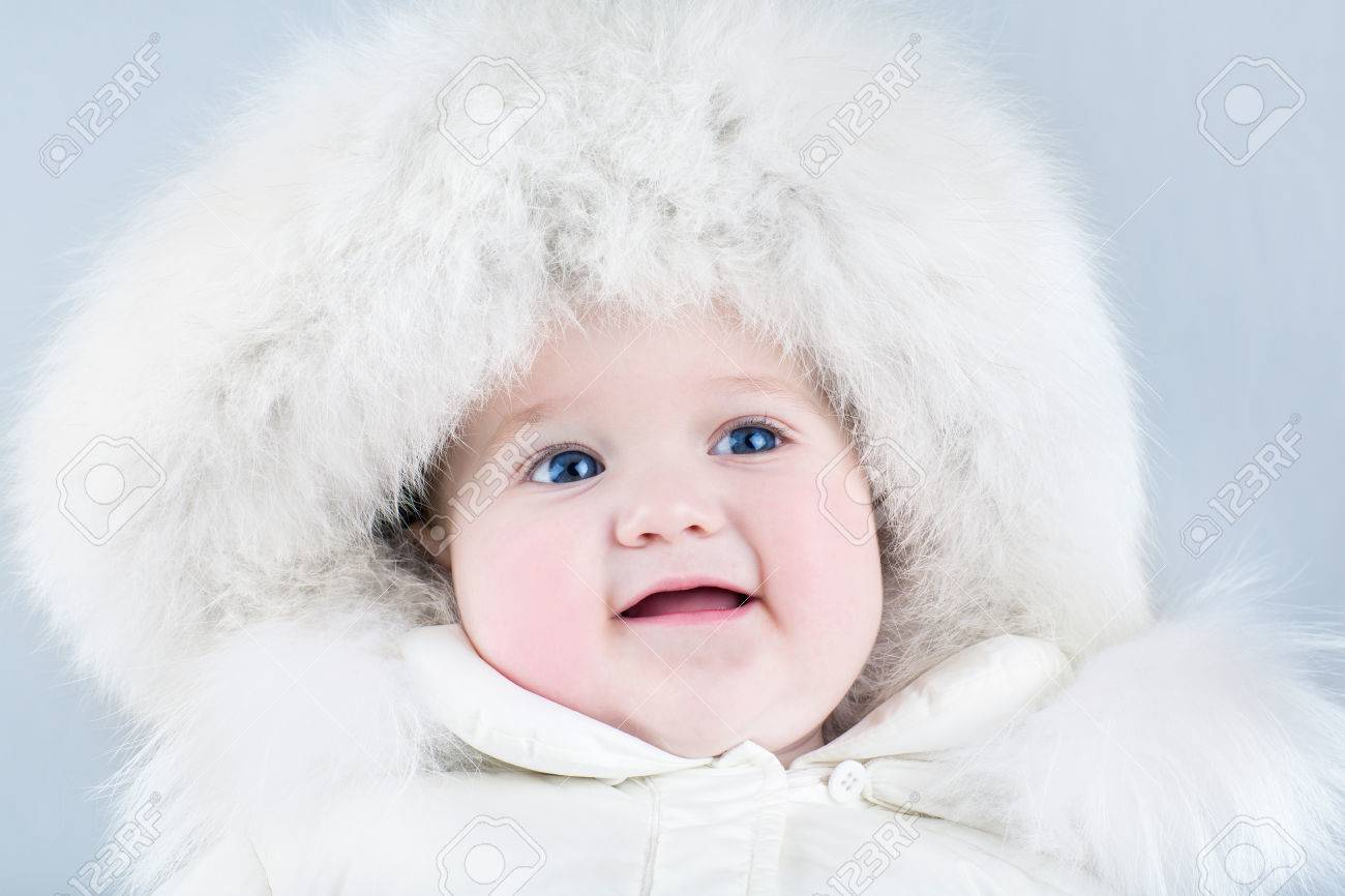 ... light blue background. Funny sweet baby girl wearing a big fur hat and  a white winter snow suit on 64fe31976d34