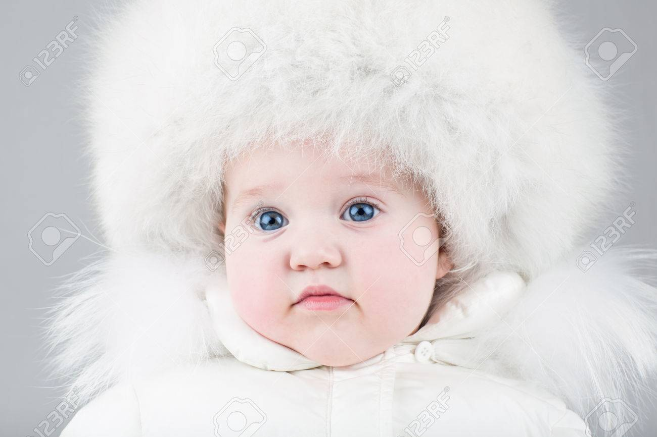 8464b41ccdfa Funny Little Baby Girl Wearing A Huge Fur Hat And A White Warm ...