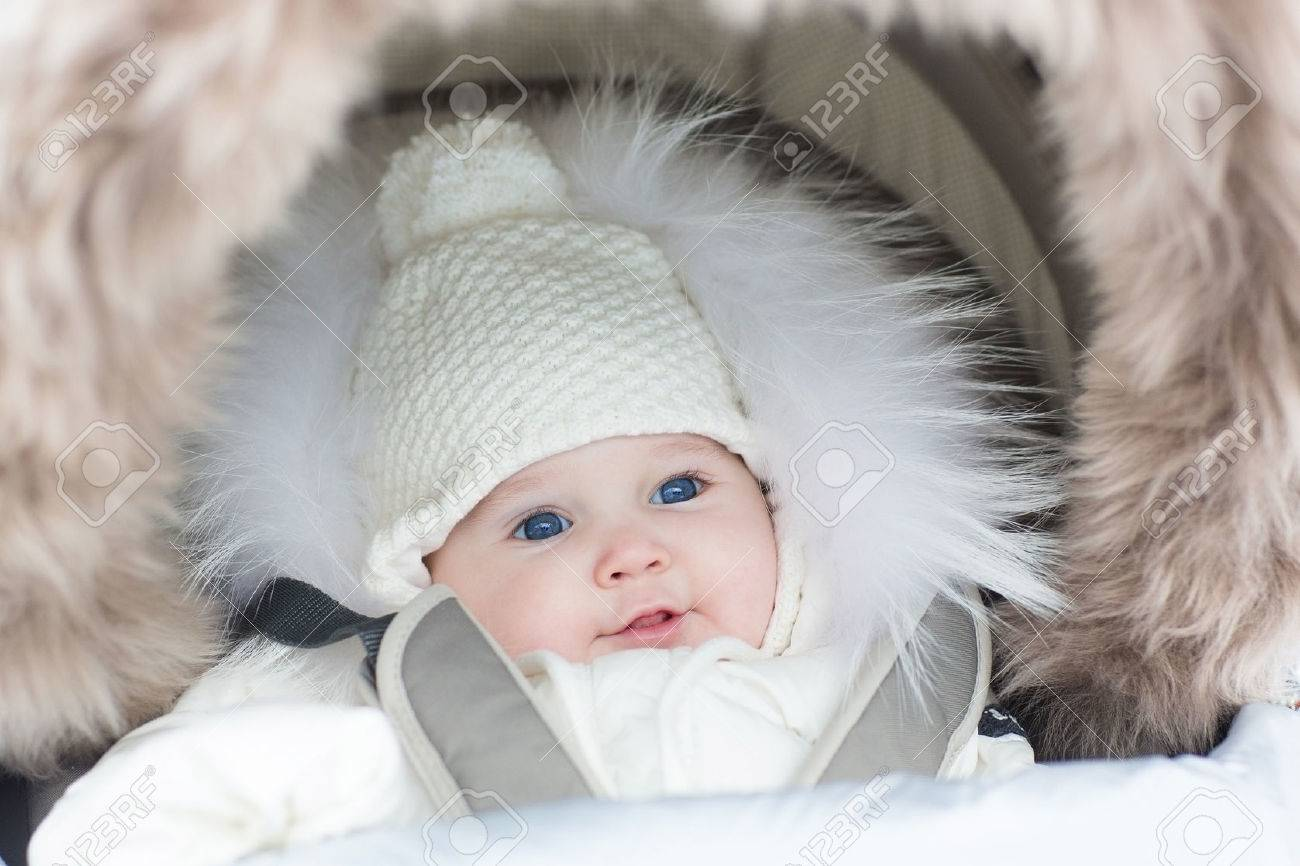 da015c229d4a Adorable Smiling Baby Girl In A Warm Stroller Wearing A Winter ...