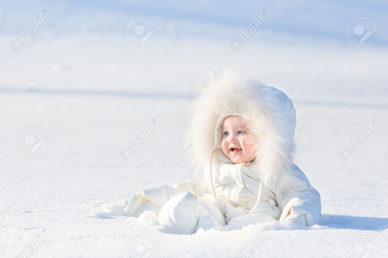 895a96a49 Adorable Laughing Baby Girl In A Warm White Snow Suit Playing ...