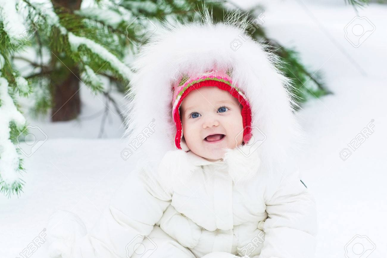 9a1cc31bf Funny Laughing Baby Girl Sitting In Snow Under A Christmas Tree ...