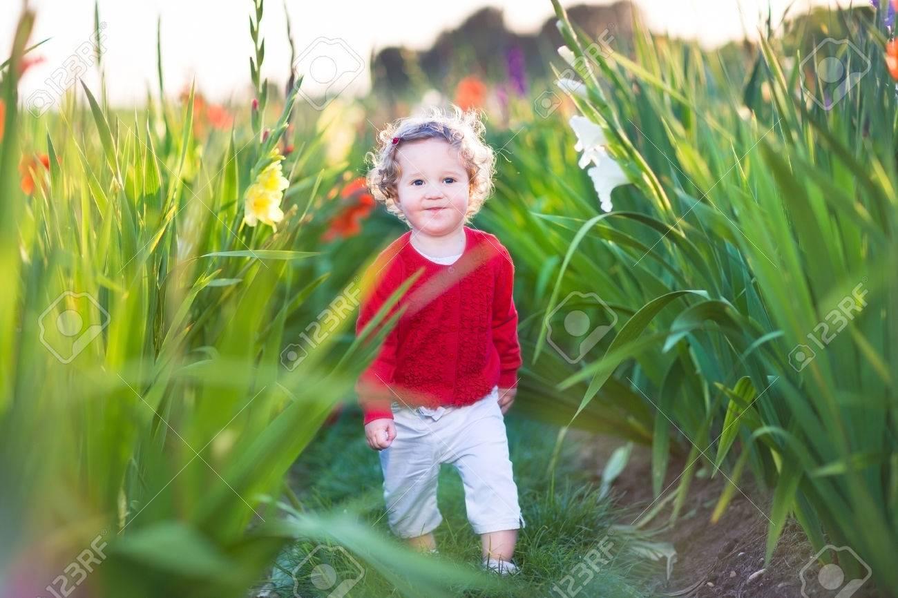 cute little baby girl walking in a field on flowers on a farm