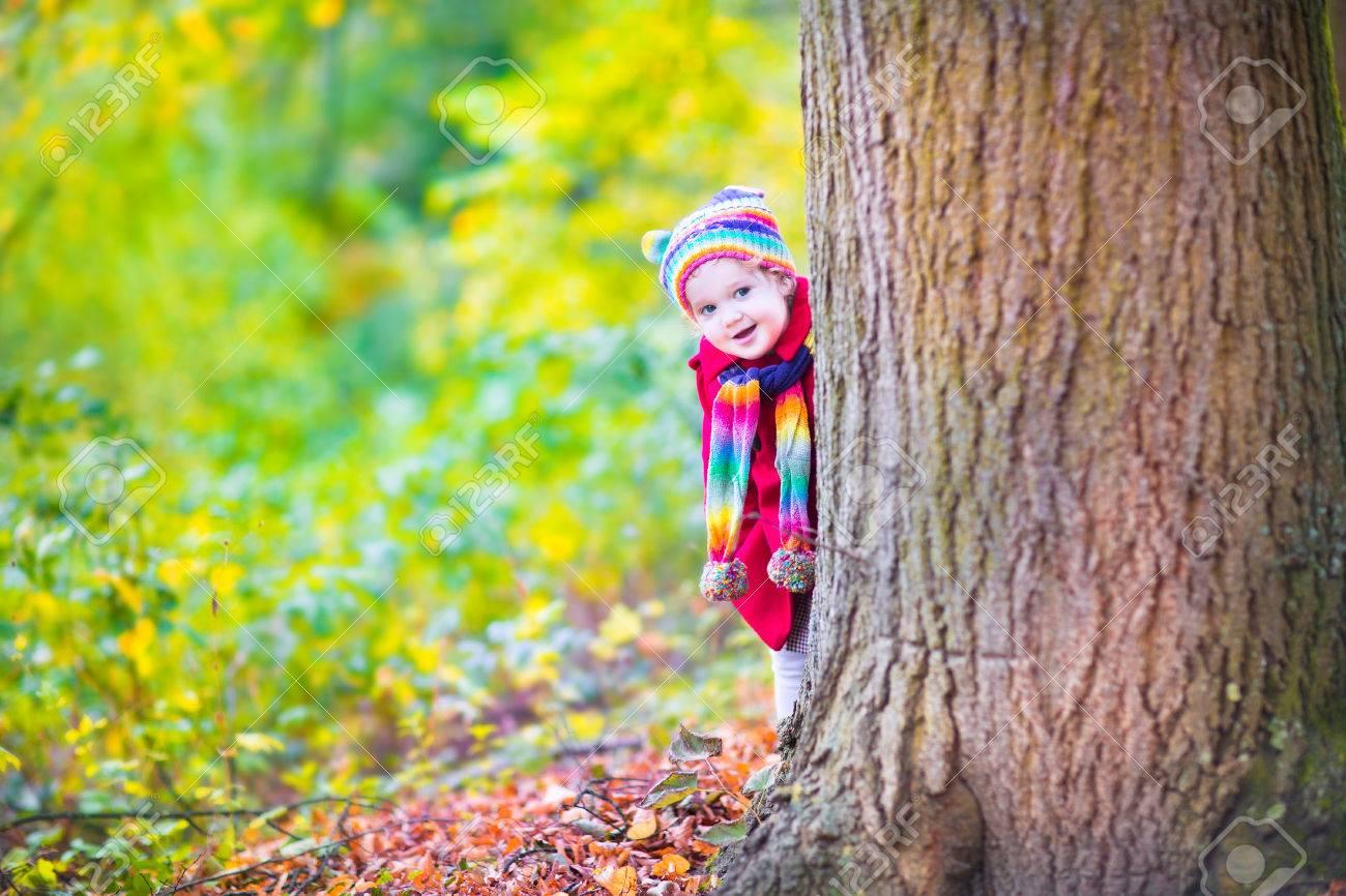 Drôle Petite Fille De Bébé Dans Une Veste Rouge Et Coloré Bonnet Tricoté Et  écharpe Jouant Avec Feuilles D érable Dorées Dans Un Parc Ensoleillé Avec  Des ... 36570c86cb7