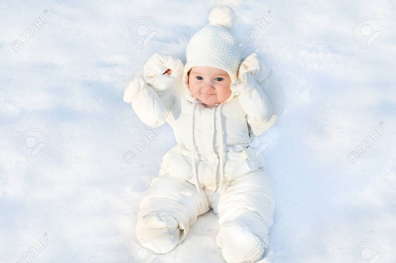 b0a1c8347efa Funny Little Baby Sitting In Fresh Snow Wearing A White Jacket ...