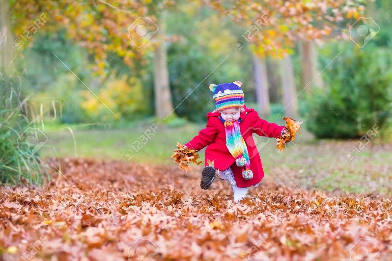 Banque d images - Douce petite fille portant un manteau rouge et coloré  tricoté chapeau et écharpe marche dans un parc d automne jouant avec des  feuilles d  ... 8b0b9d91dd0