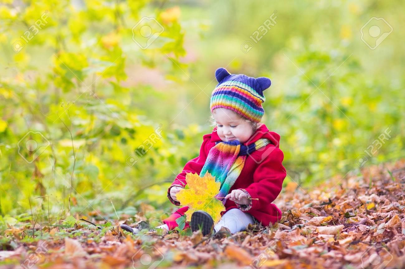 Adorable fille de bébé dans un manteau rouge et coloré bonnet tricoté et  écharpe en jouant 668a85b2626