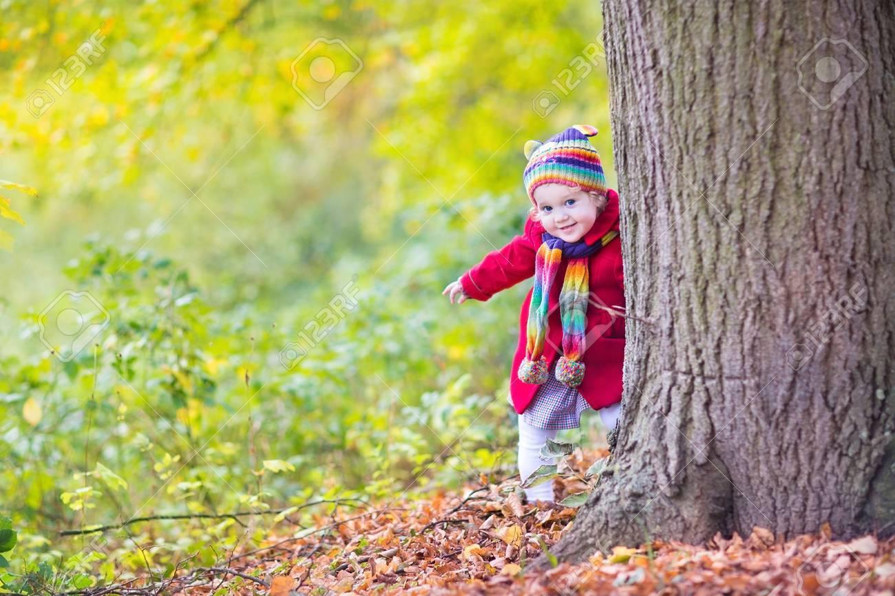 Banque d images - Bébé doux drôle dans un manteau rouge et un chapeau coloré  et écharpe tricotée se cachant derrière un grand vieil arbre dans un  magnifique ... 363810321a4