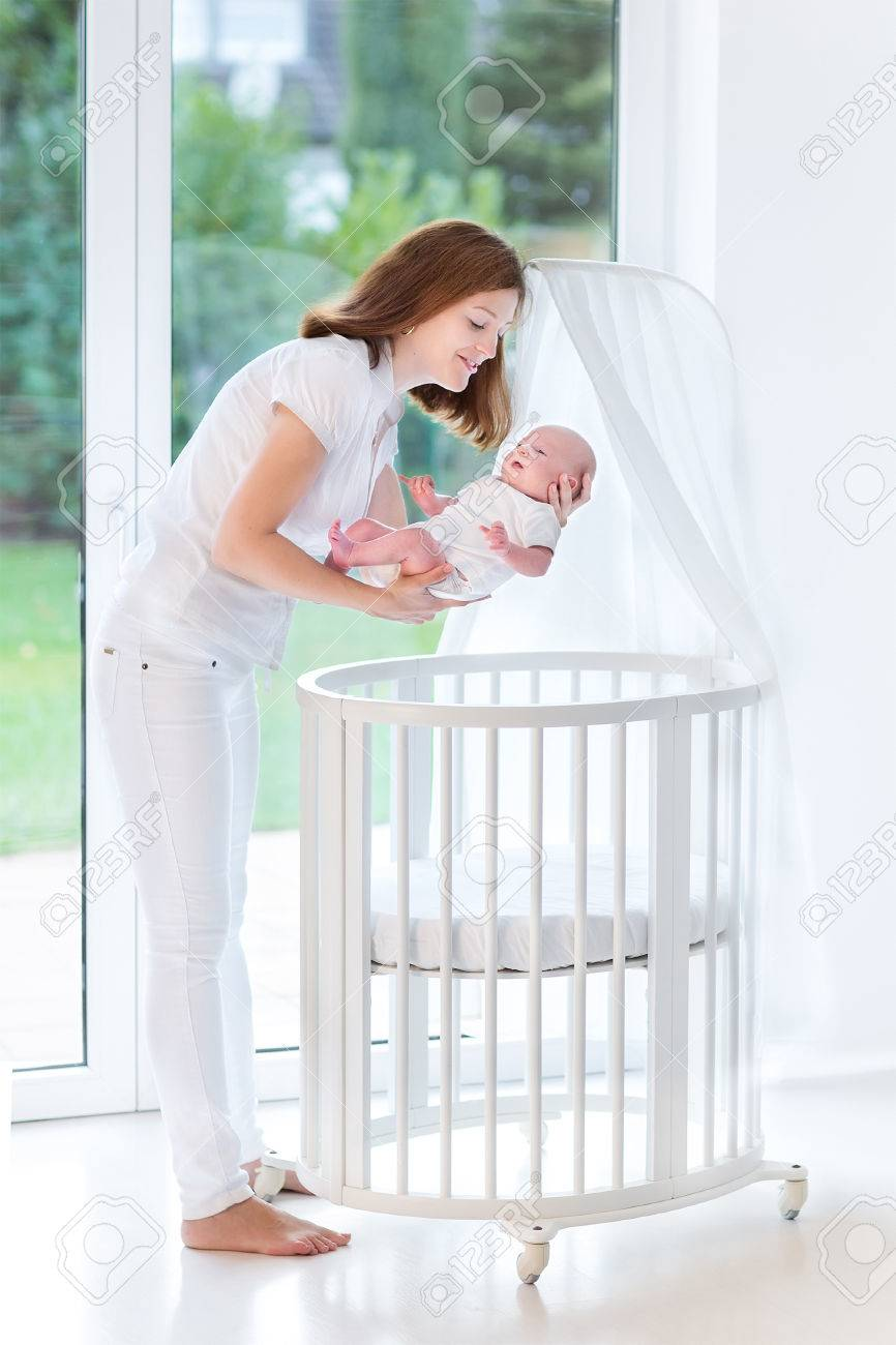 Young mother putting her newborn baby to sleep in a white round crib with canopy next & Young Mother Putting Her Newborn Baby To Sleep In A White Round ...