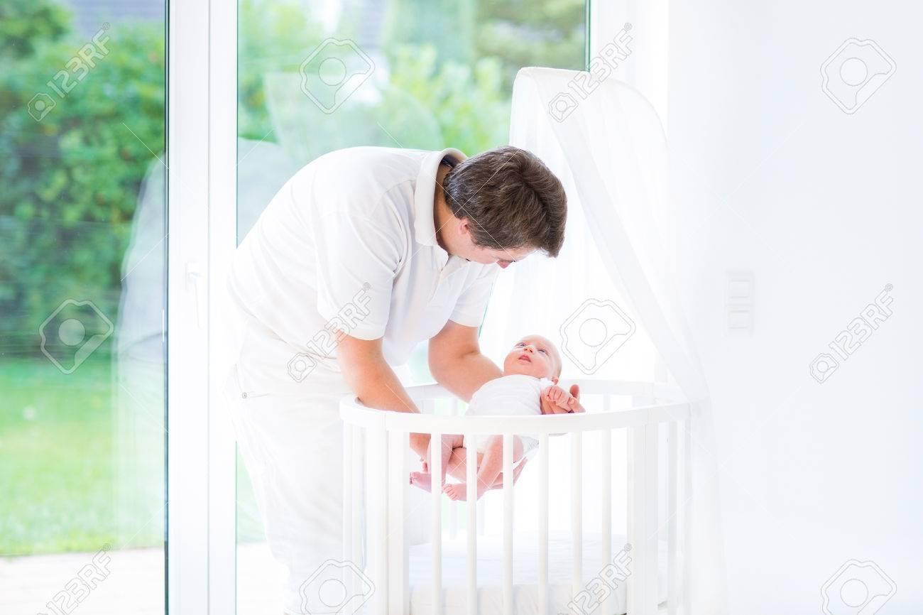 Junge lächelnde vater legte seinen neugeborenen baby in einem weißen