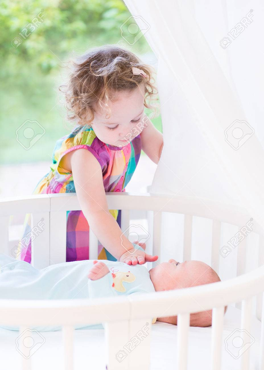 Baby cribs big w - Cute Toddler Girl Playing With Her Newborn Baby Brother Laying In A White Round Crib Next