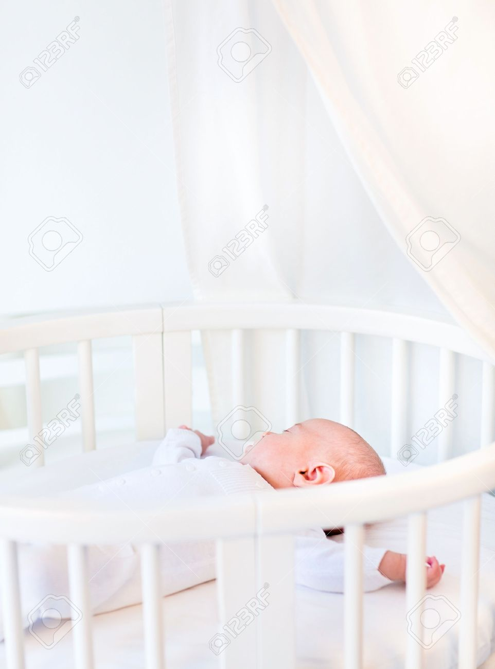 Portrait of a newborn baby boy sleeping in a white round crib with canopy  Stock Photo