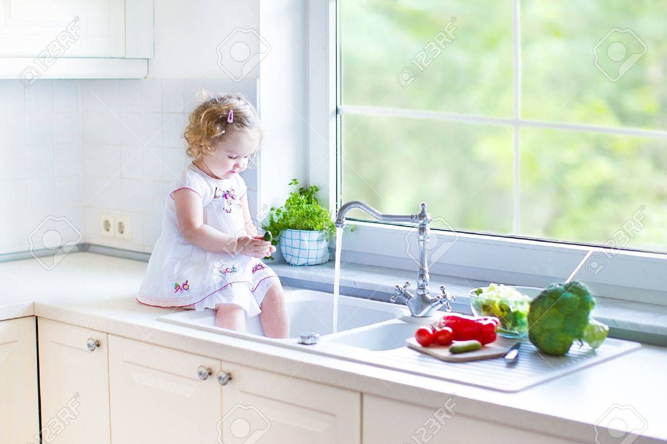 Cute Funny Toddler Girl Washing Vegetables In A Kitchen Sink