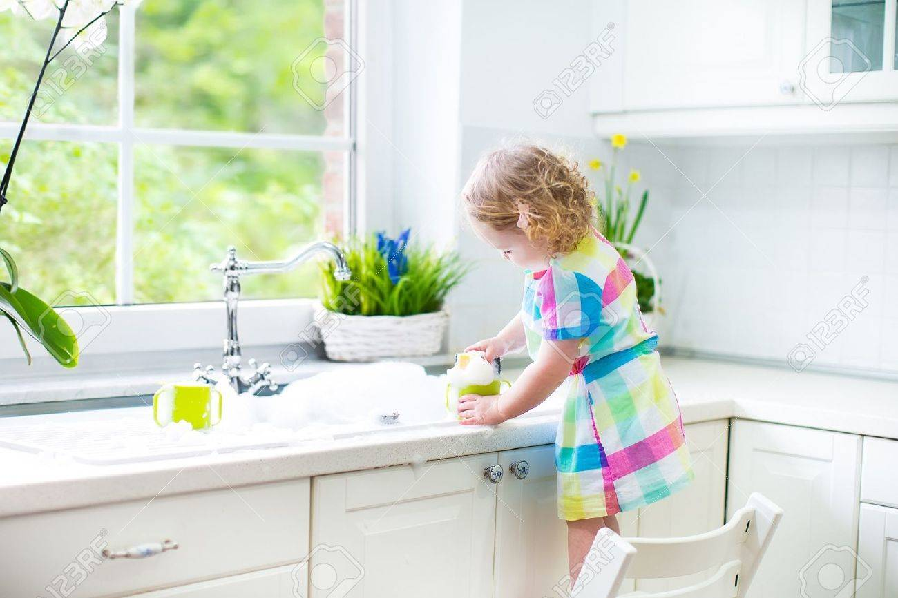 Cute Curly Toddler Girl In A Colorful Dress Washing Dishes, Cleaning ...