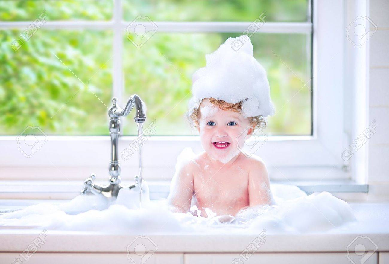 funny little baby girl with wet curly hair taking a bath in a