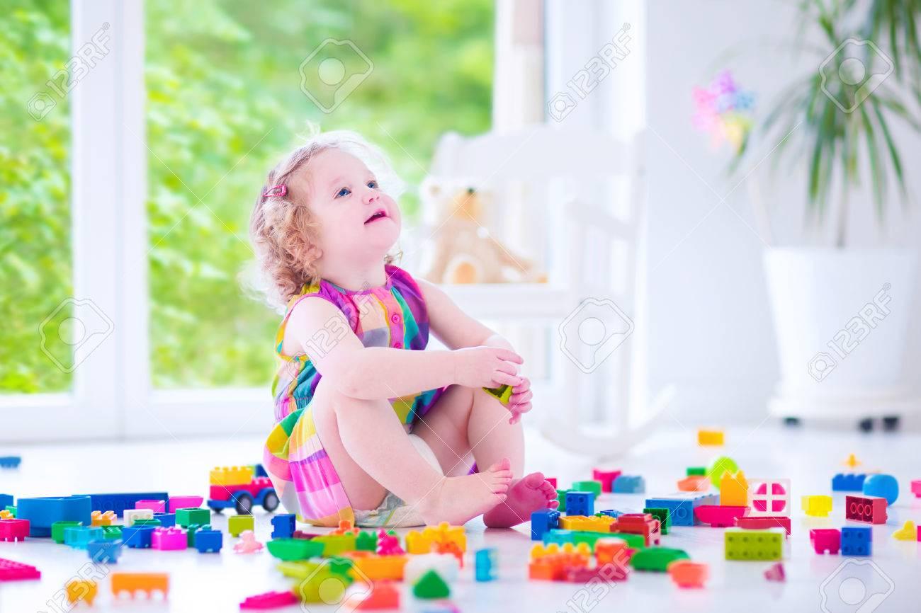 Bedårande skratta litet barn, söt liten tjej med lockigt hår klädd ...