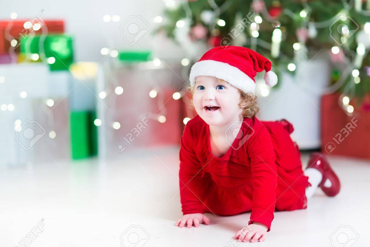 91e3937bf Laughing Happy Baby Girl In A Red Dress And Santa Hat Playing ...