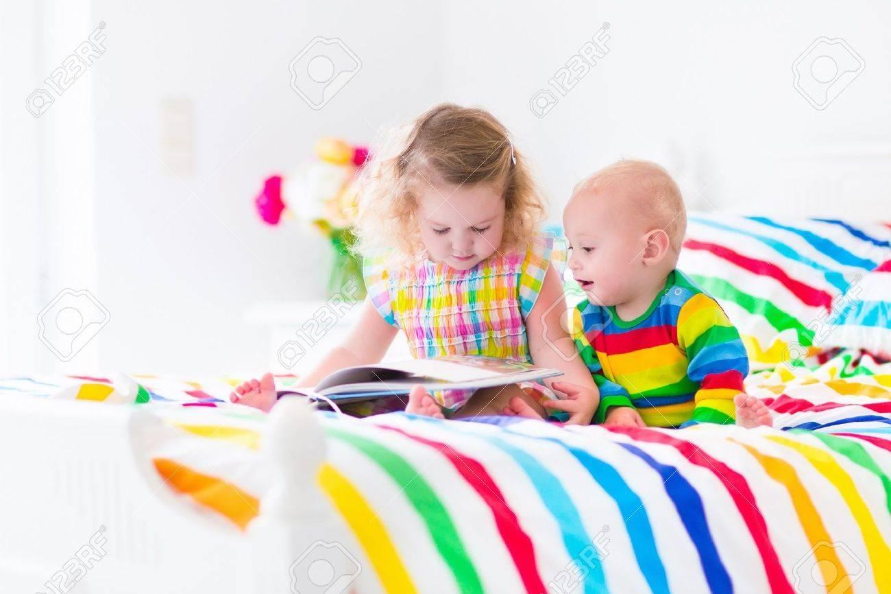 2 人の子供、かわいい巻き毛の小さな幼児の女の子と面白い赤ちゃん
